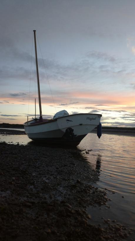 Boat against the September sunset in Blakeney Harbour