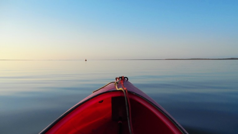 Winter kayaking on a flat calm blue sea in Brancaster Harbour