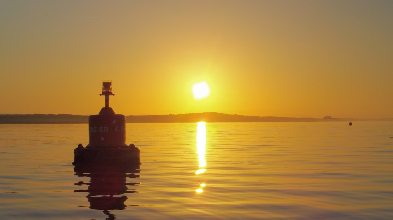 Sunset and channel buoy in Brancaster Harbour